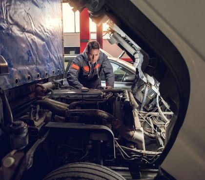 Mężczyzna naprawia silnik ciężarówki