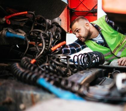 Osoba naprawiająca ciężarówkę